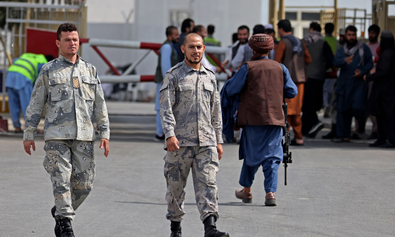 Afghan policemen walk past a Taliban fighter (R) outside the airport in Kabul on Sunday. — AFP