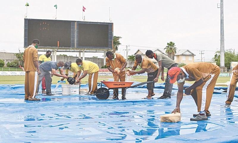 سبینا پارک جمیکا میں گراؤنڈ اسٹاف کورز پر سے پانی صاف کرتے ہوئے— تصویر: رائٹرز/ اے پی