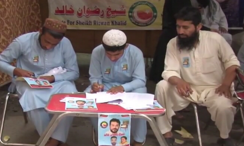 Political workers seen at an election camp in Peshawar on Sunday. — DawnNewsTV