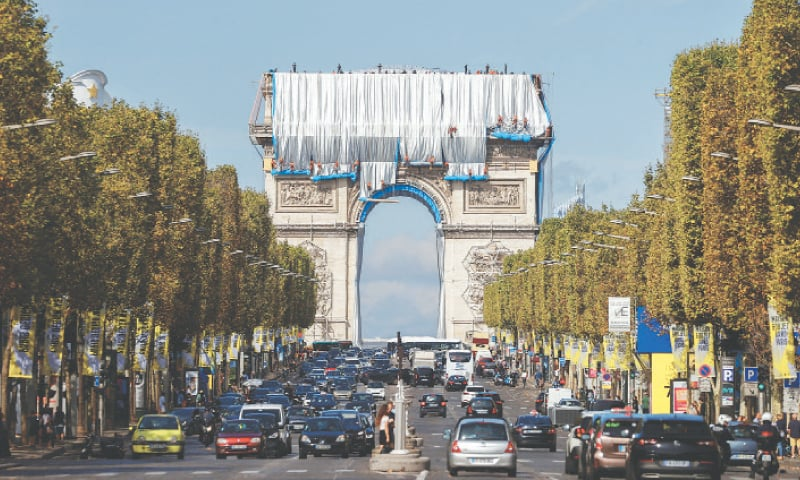WORKERS install a shimmering wrapper to envelop a Paris landmark, the Arc de Triomphe, in a posthumous installation by artist Christo on the Champs Elysee avenue.—Reuters
