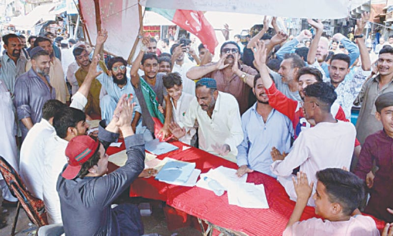 YOUTHS crowd an election camps to find their names in the voters' lists on Sunday.—APP
