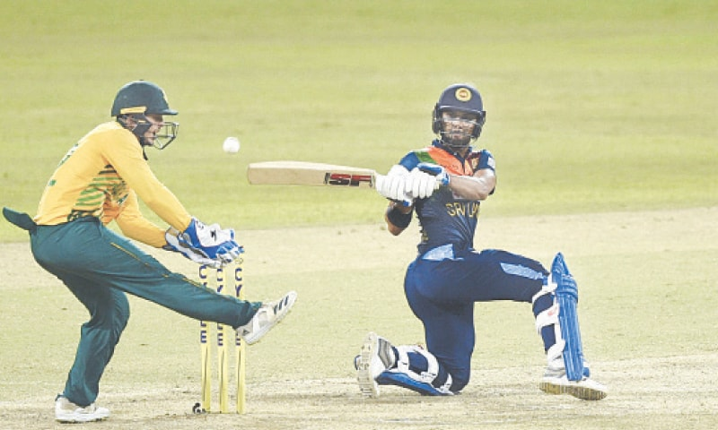 SRI LANKA'S Dinesh Chandimal plays a reverse sweep as  South African wicket-keeper Quinton de Kock reacts during the second Twenty20 International at the R. Premadasa Stadium on Sunday.—AFP