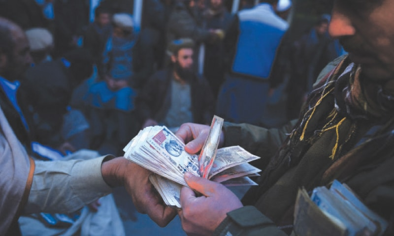 In this file photo, Afghan money changers count banknotes at the currency exchange Sarayee Shahzada market in Kabul. With the Taliban in control and foreign aid blocked, Afghanistan's economy is likely to contract sharply as it faces a shortage of cash, the nation's former central bank chief said last week.—AFP