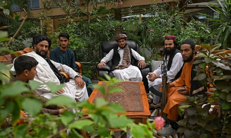 In this picture taken on September 11, Taliban fighters sit in the greenhouse yard at the home of the Afghan warlord Abdul Rashid Dostum in the Sherpur neighborhood of Kabul. — AFP
