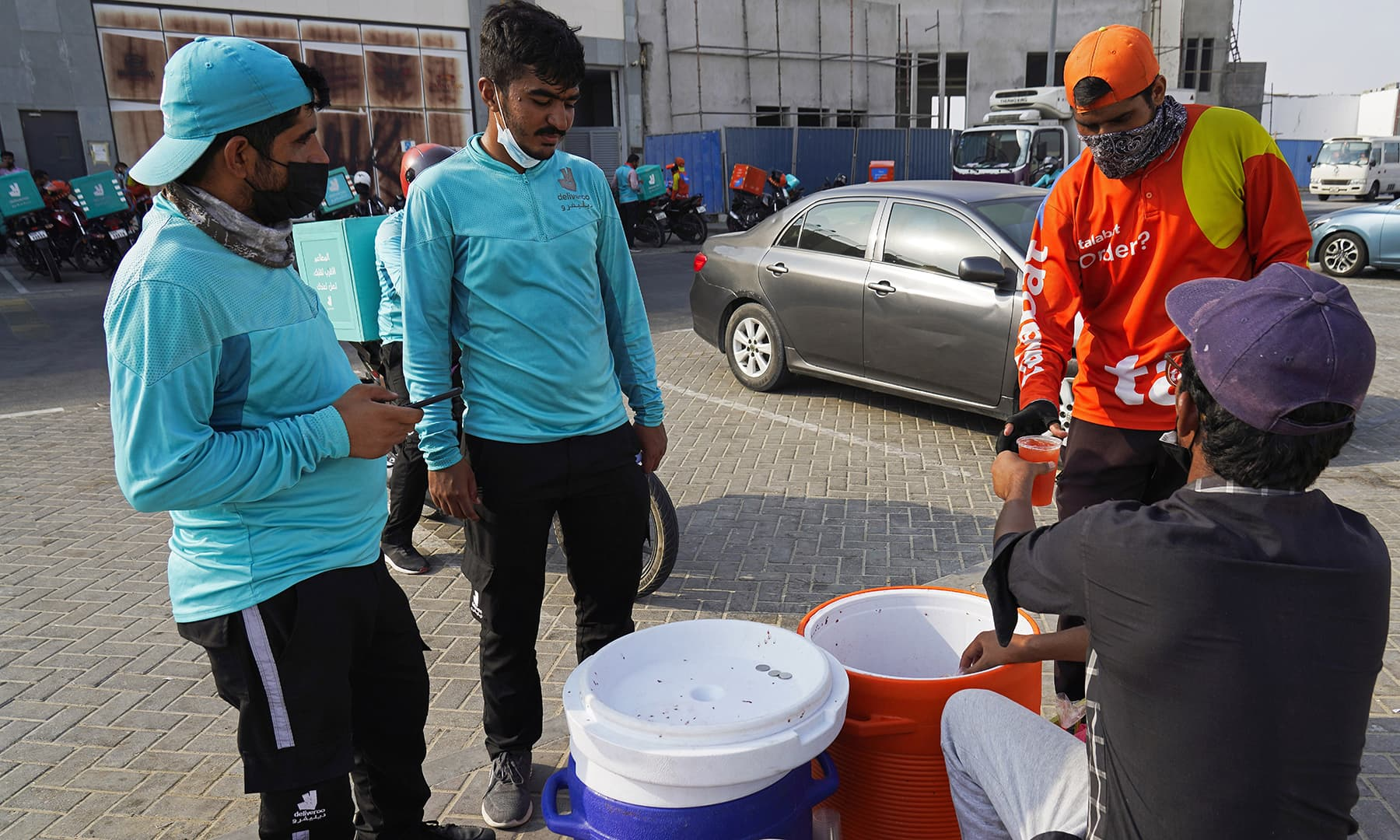 Motorcycle delivery drivers take a break and buy juice, in Dubai, United Arab Emirates, on Sept 9. — AP