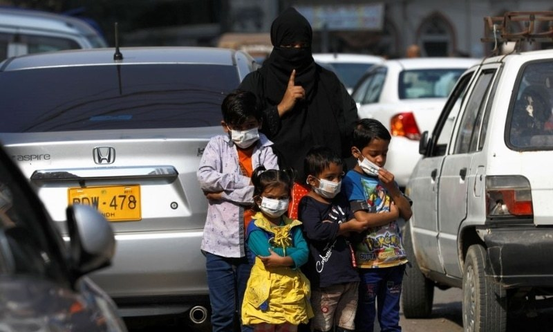 Children wear protective masks as they wait with their mother to cross the road in Karachi on January 15. — Reuters/File