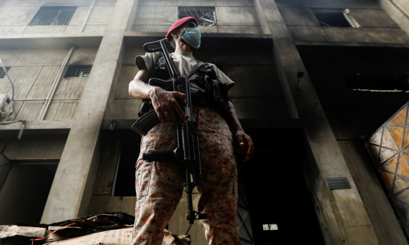 A Rangers official stands guard, after a fire broke out at a multi-storey chemical factory, in Karachi, on August 27.— Reuters/File