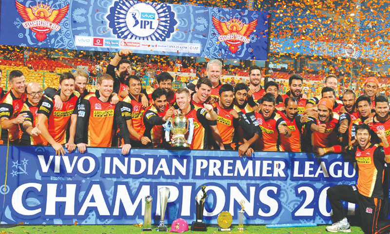 Players and officials of Sunrisers Hyderabad pose with the trophy after winning the IPL final at the M. Chinnaswamy Stadium. — AFP/File
