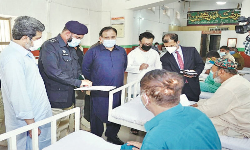 CHIEF Minister Usman Buzdar talks to the prisoners admitted to the Sialkot District Jail hospital. — Dawn