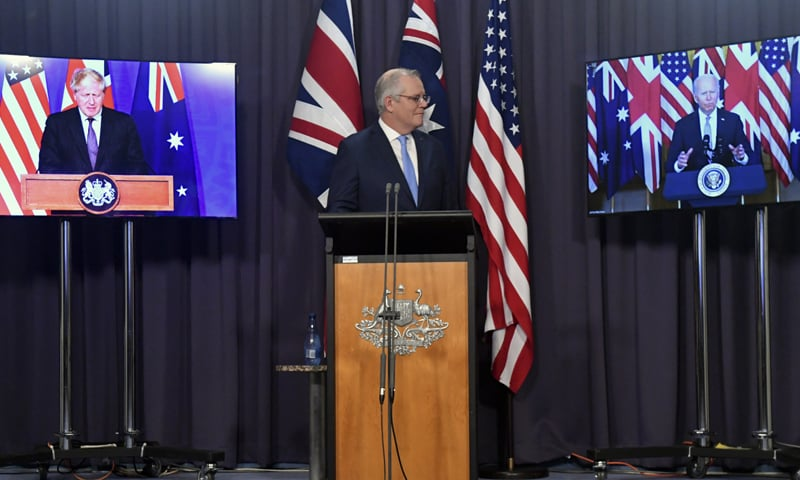 Australia's Prime Minister Scott Morrison, center, appears on stage with video links to Britain's Prime Minister Boris Johnson, left, and US President Joe Biden at a joint press conference at Parliament House in Canberra. — AP
