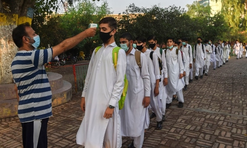 A teacher checks the body temperature of a student as others stand in queue upon their arrival at a school in Peshawar on September 16. — AFP