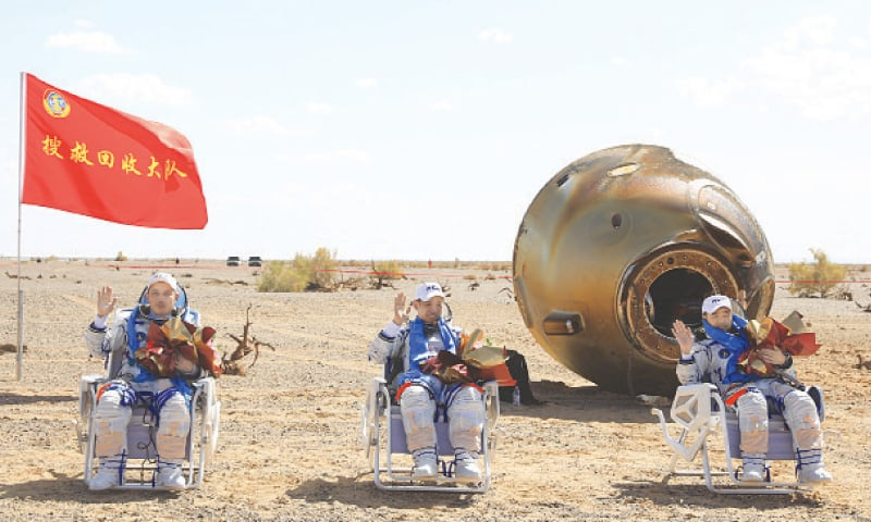 THIS photo released by Xinhua News Agency shows astronauts Tang Hongbo (left), Nie Haisheng (centre) and Liu Boming waving to admirers after landing at the Dongfeng landing site in northern China.—AP