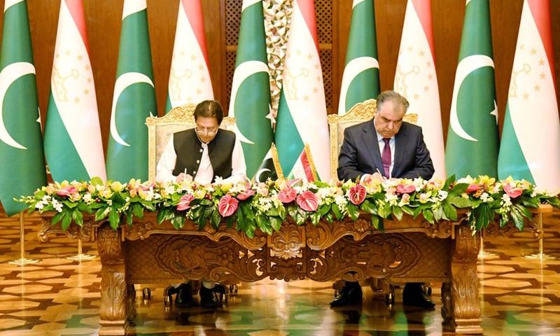 Prime Minister Imran Khan (L) and  Tajik President Emomali Rahmon (R) sign the joint statement on establishment of strategic partnership between Pakistan and Tajikistan on Friday. — Photo courtesy PID website