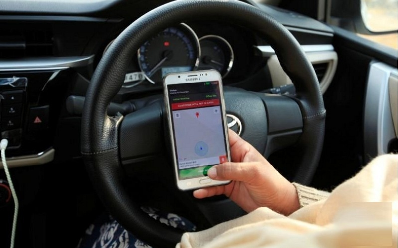 """In this file photo, a """"captain"""" of Careem checks her work app before driving her car in Islamabad on Dec 7, 2016. — Reuters/File"""