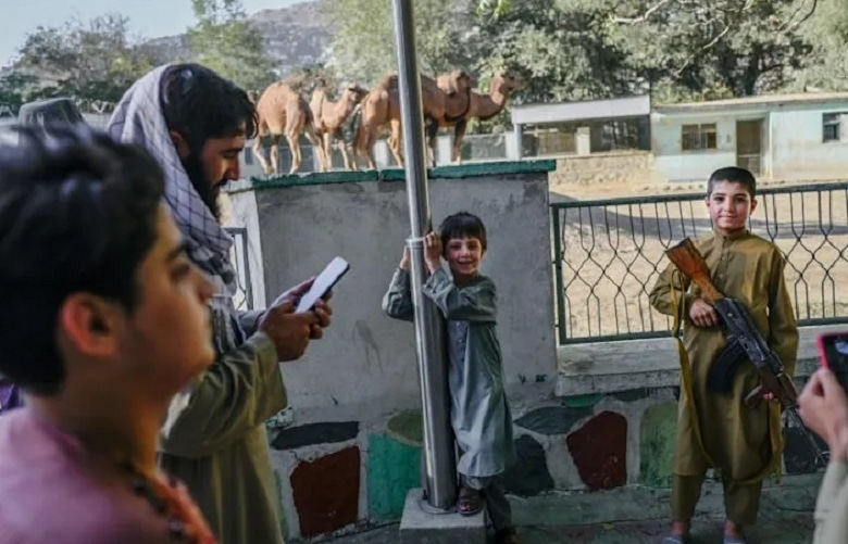 A group of Taliban gunmen offered their rifles to boys as young as eight, who took snaps with their mobile phones. — AFP