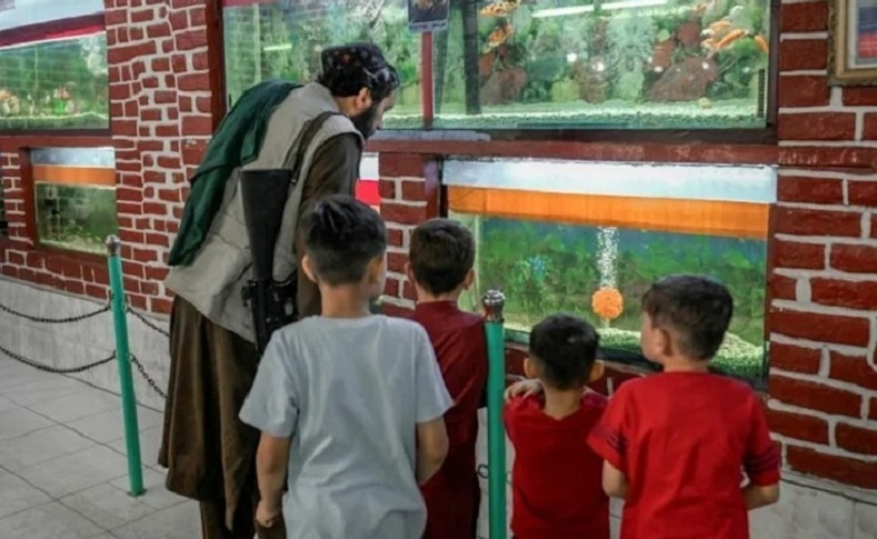 Heavily armed Taliban gunmen peered into the aquarium and reptile house at Kabul Zoo on Friday. — AFP