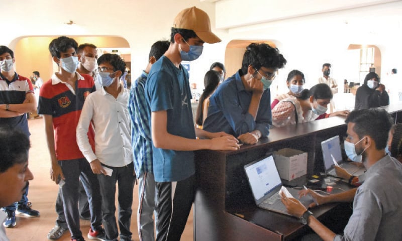 Youngsters stand at a counter to get themselves registered for Covid-19 vaccination at the F-9 Park mass vaccination centre in Islamabad on Saturday. — Online