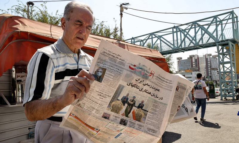 """An Iranian man reads a copy of the daily newspaper """"Etalaat"""" bearing the headline """"Iran is a new member of the Shanghai Cooperation Organisation"""", at a kiosk in the capital Tehran, on Saturday. — AFP"""