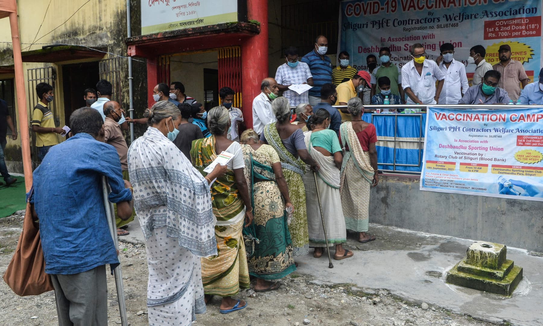 Underprivileged people stand in a queue as they wait to receive a dose of the Covishield vaccine against the Covid-19 coronavirus at a vaccination camp in Siliguri, India, on September 19, 2021. — AFP