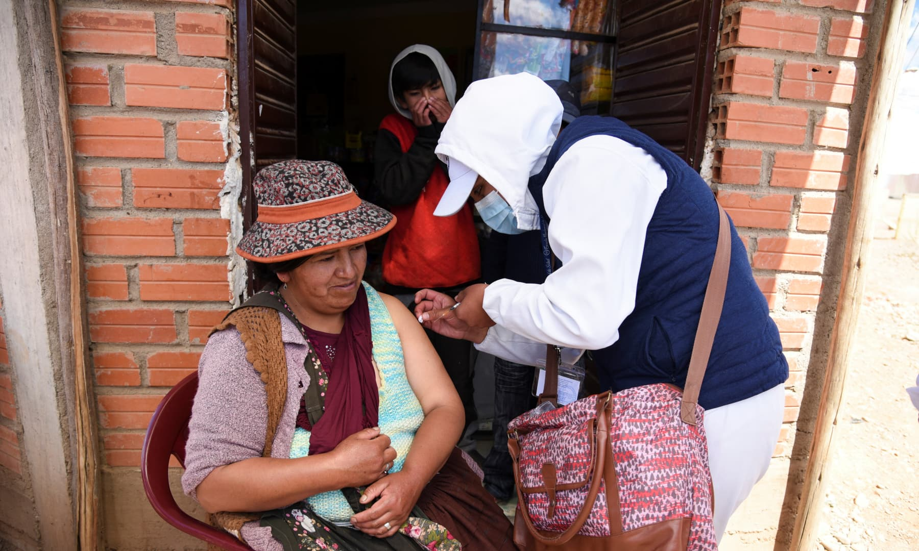 Shop owner Severina Cruz receives the AstraZeneca vaccine against the coronavirus as healthcare workers go from house to house to inoculate residents, in El Alto, Bolivia, on September 17, 2021. — Reuters