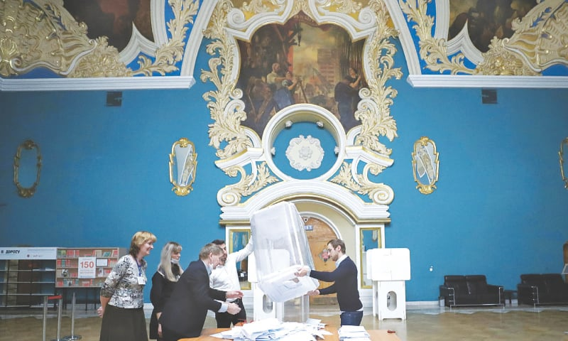 MOSCOW: Members of a local election commission empty a ballot box after polls closed on Sunday.—Reuters