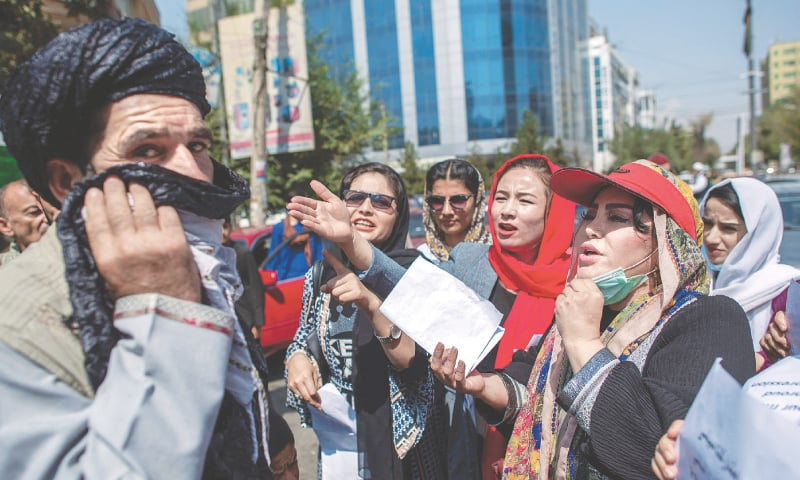 Women converse with a man during the demonstration in front of the former ministry of women affairs.—AFP