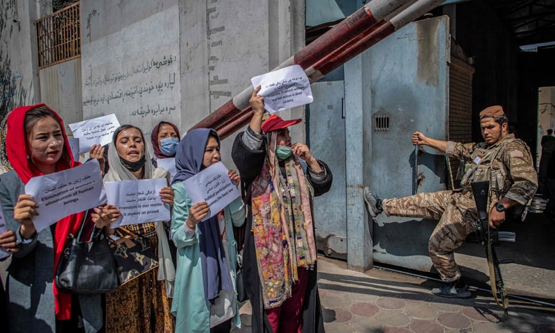 A Taliban member watches as Afghan women hold placards during a demonstration demanding better rights for women in front of the former ministry of women affairs in Kabul. — AFP/File