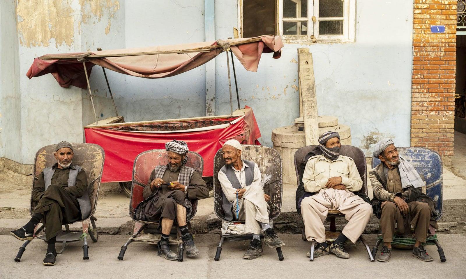 افغان مزدور کابل کی گلی میں گاہک کا انتظار کررہے ہیں —فوٹو: اے پی