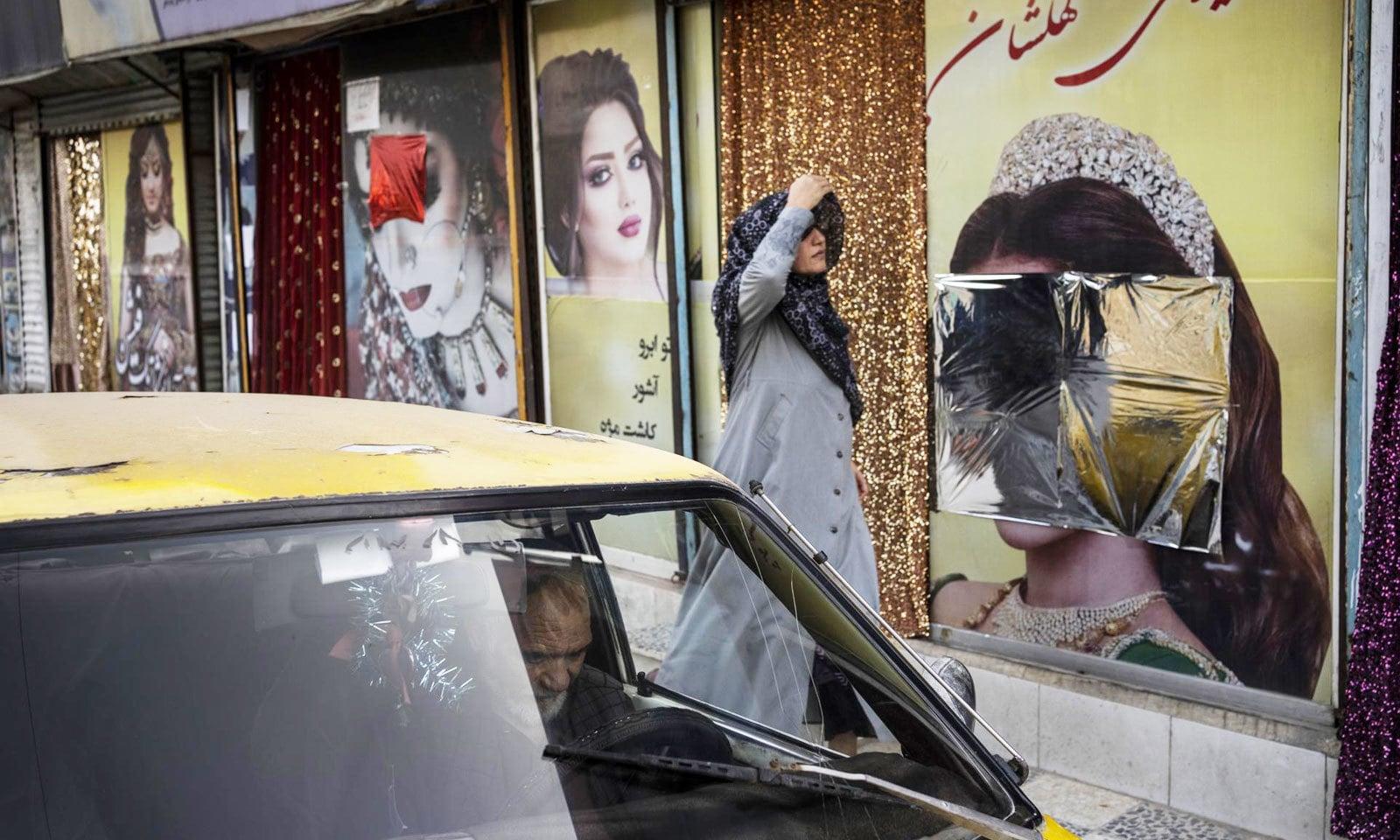 خاتون 12 ستمبر کو کابل کے ایک بیوٹی پارلر کے سامنے سے گزرہی ہیں — فوٹو: اے پی
