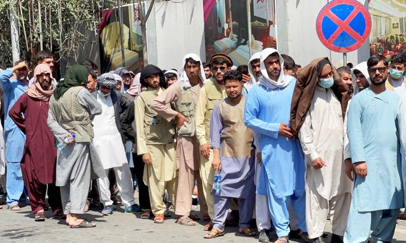 لوگ یکم ستمبر کو کابل کے ایک بینک کے باہر رقم کے حصول کے لیے قطار میں کھڑے ہوئے ہیں—فوٹو: رائٹرز
