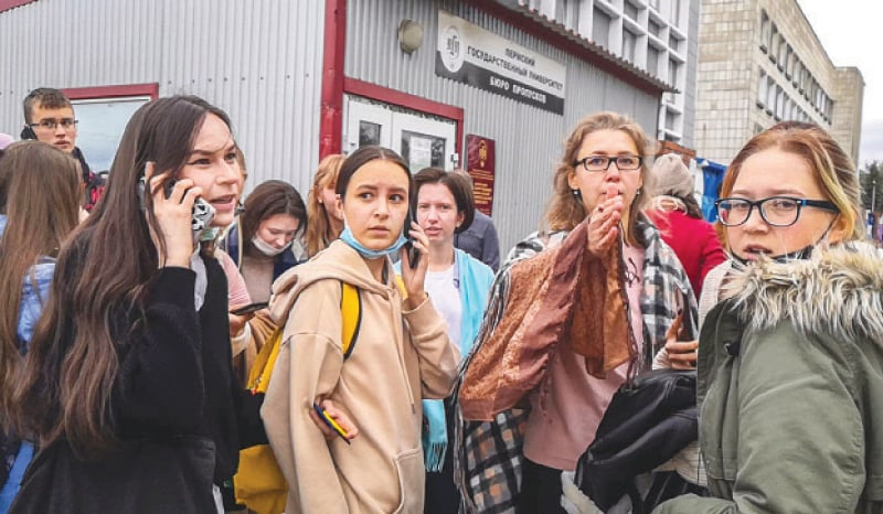 Students evacuate a building of the Perm university campus following the shooting on Monday.—AFP