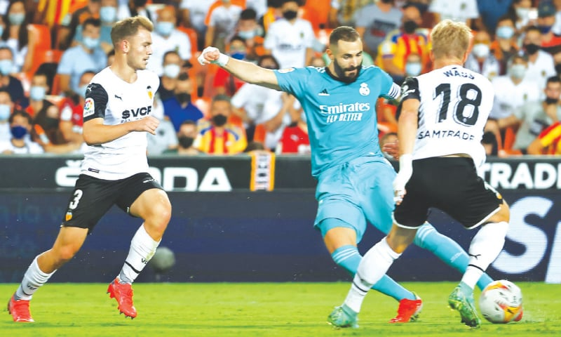 VALENCIA: Real Madrid's Karim Benzema shoots in front of Valencia's Daniel Wass during their La Liga match at the Mestalla.—AFP