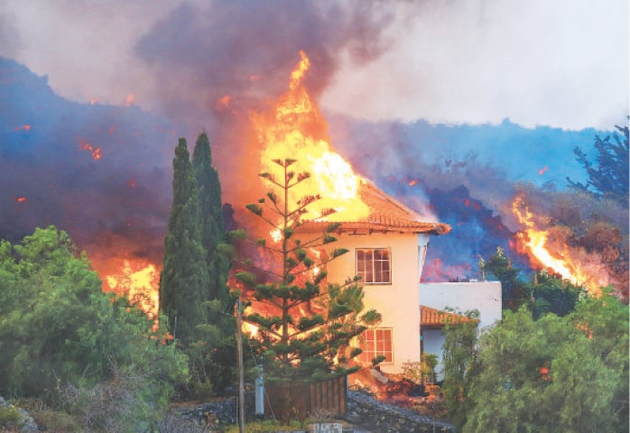 A HOUSE burns after the eruption.—Reuters