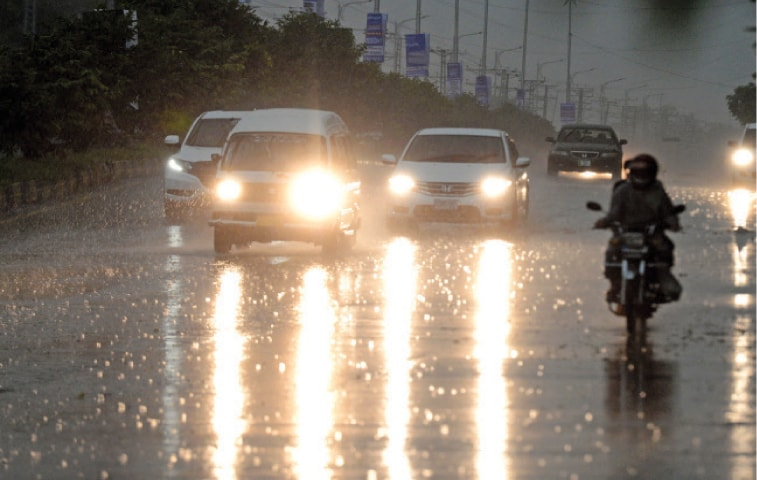 Vehicles travel on Club Road during rain in Islamabad on Monday. — Photo by Mohammad Asim