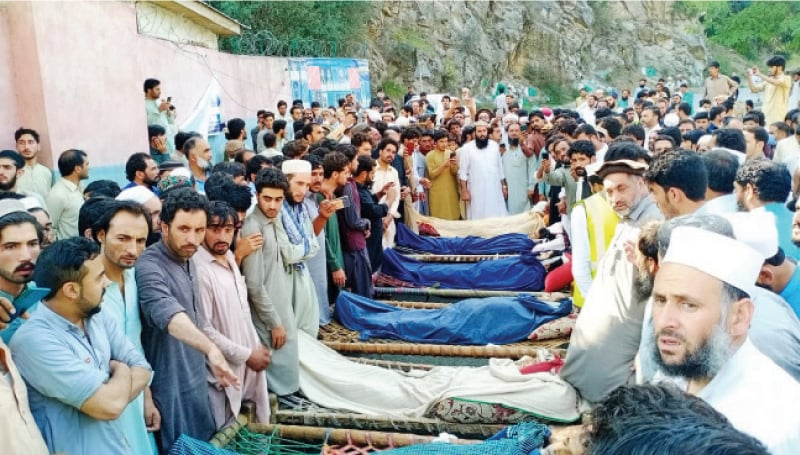Protesters place bodies on Dir-Peshawar Road on Monday to demand arrest of killers. — Dawn