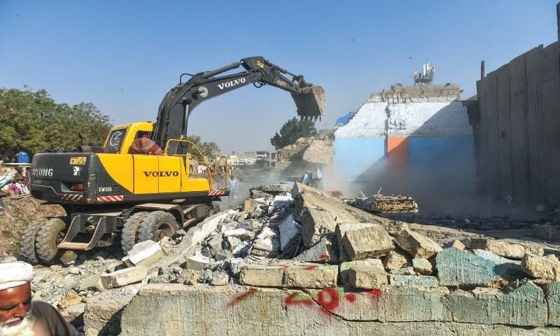 This file photo shows houses built along Karachi's Gujjar nullah being bulldozed. — White Star/File
