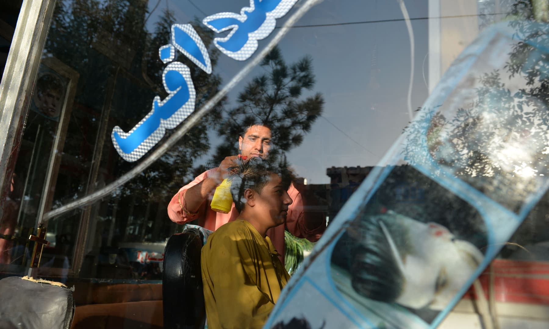 Twenty-four-year-old Nader Shah (L) attends a customer at his barbershop in Herat, Afghanistan on September 19, 2021. — AFP