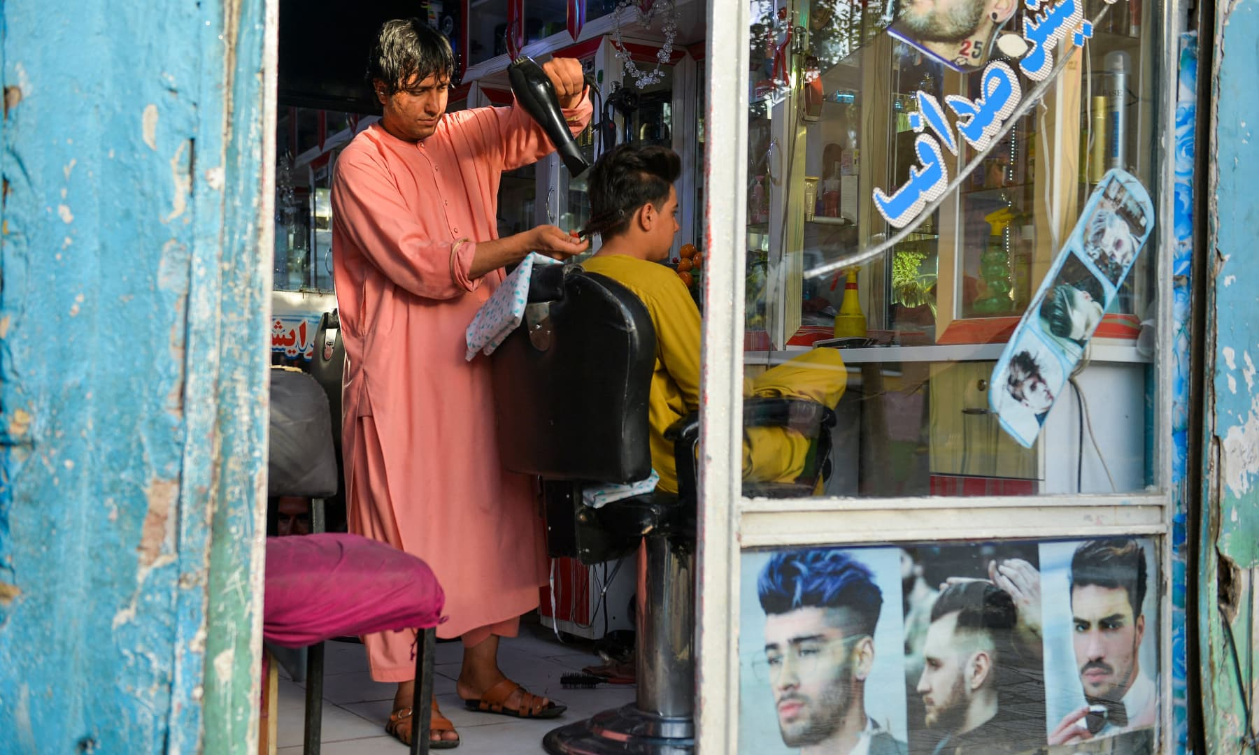A barber attends a customer at his shop in Herat, Afghanistan on September 19, 2021. — AFP