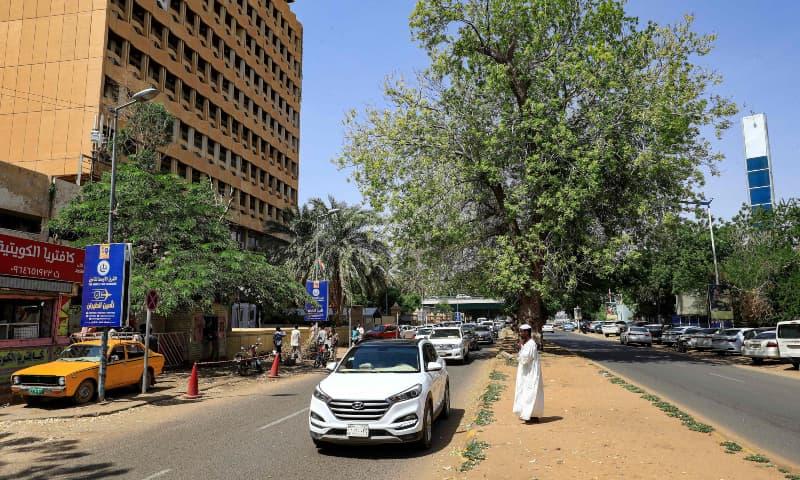Cars drive past pedestrians along the Nile Street adjacent to the Blue Nile river in Sudan's capital Khartoum on September 21. — AFP