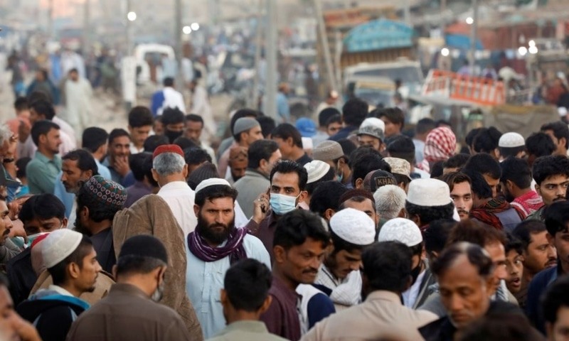 A man wearing a protective mask walks through a crowd of people along a makeshift market in Karachi on January 17. — Reuters