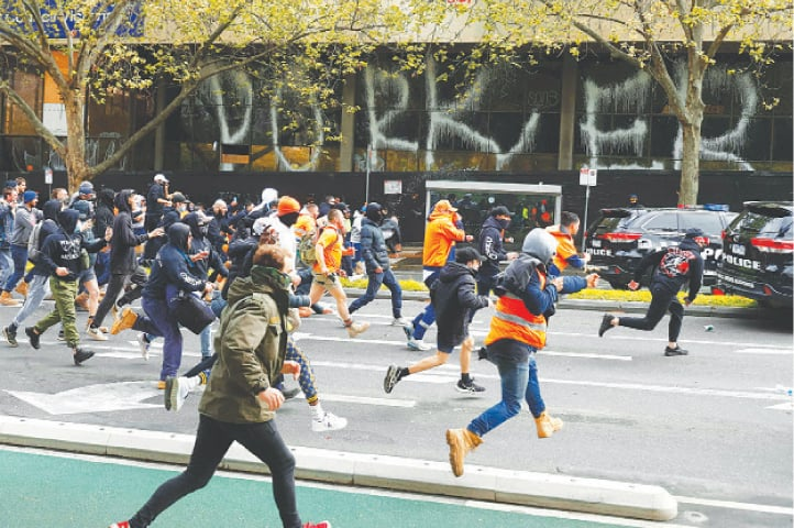 DEMONSTRATORS hit a police car during the protest in Melbourne.—AFP