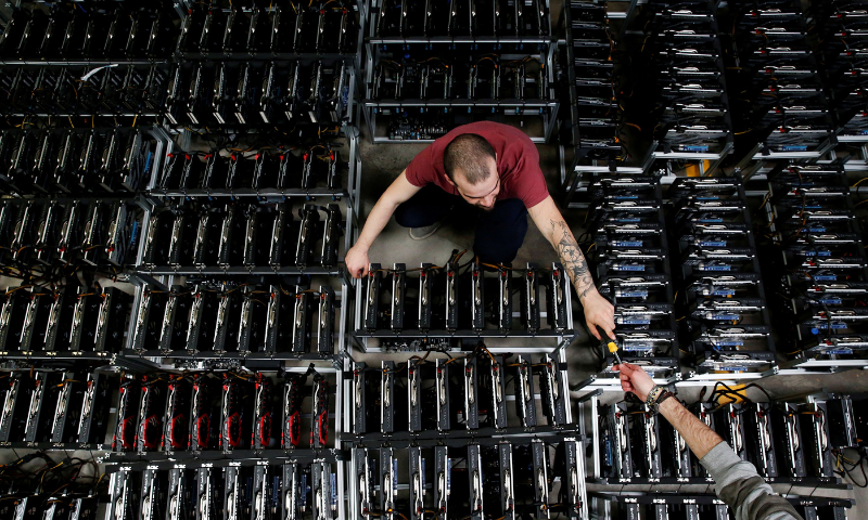 Employees work on bitcoin mining computers at Bitminer Factory in Florence, Italy. — Reuters/File