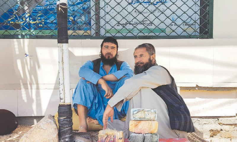 CHAMAN: With Afghan currency notes by their side, traders waiting for customers on Wednesday.—Reuters