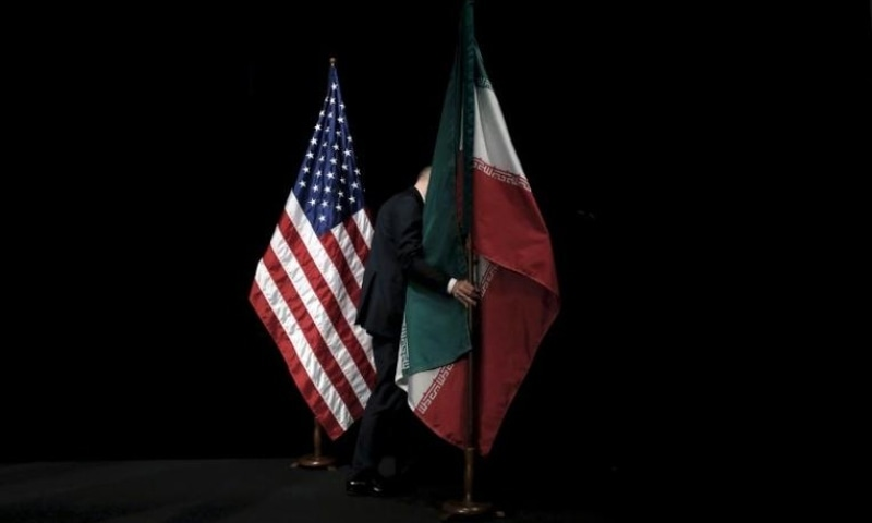 A staff member removes the Iranian flag from the stage after a group picture with foreign ministers and representatives of the US, Iran, China, Russia, Britain, Germany, France and the European Union during the Iran nuclear talks at the Vienna International Center in Austria on July 14, 2015. — Reuters