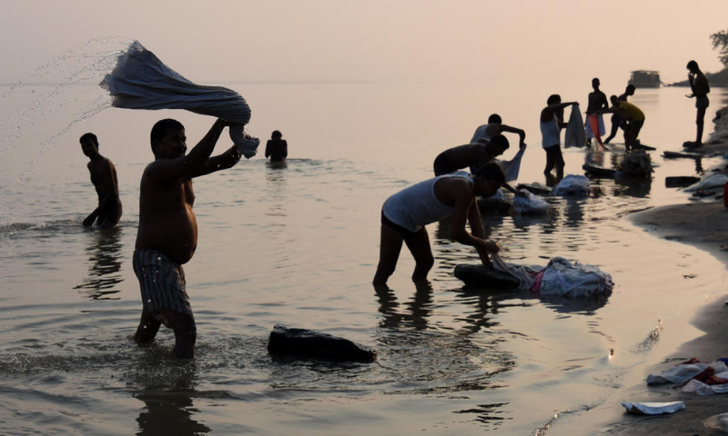 Indian washermen do laundry on the banks of the River Bhramaputra in Guwahati. — AFP/File
