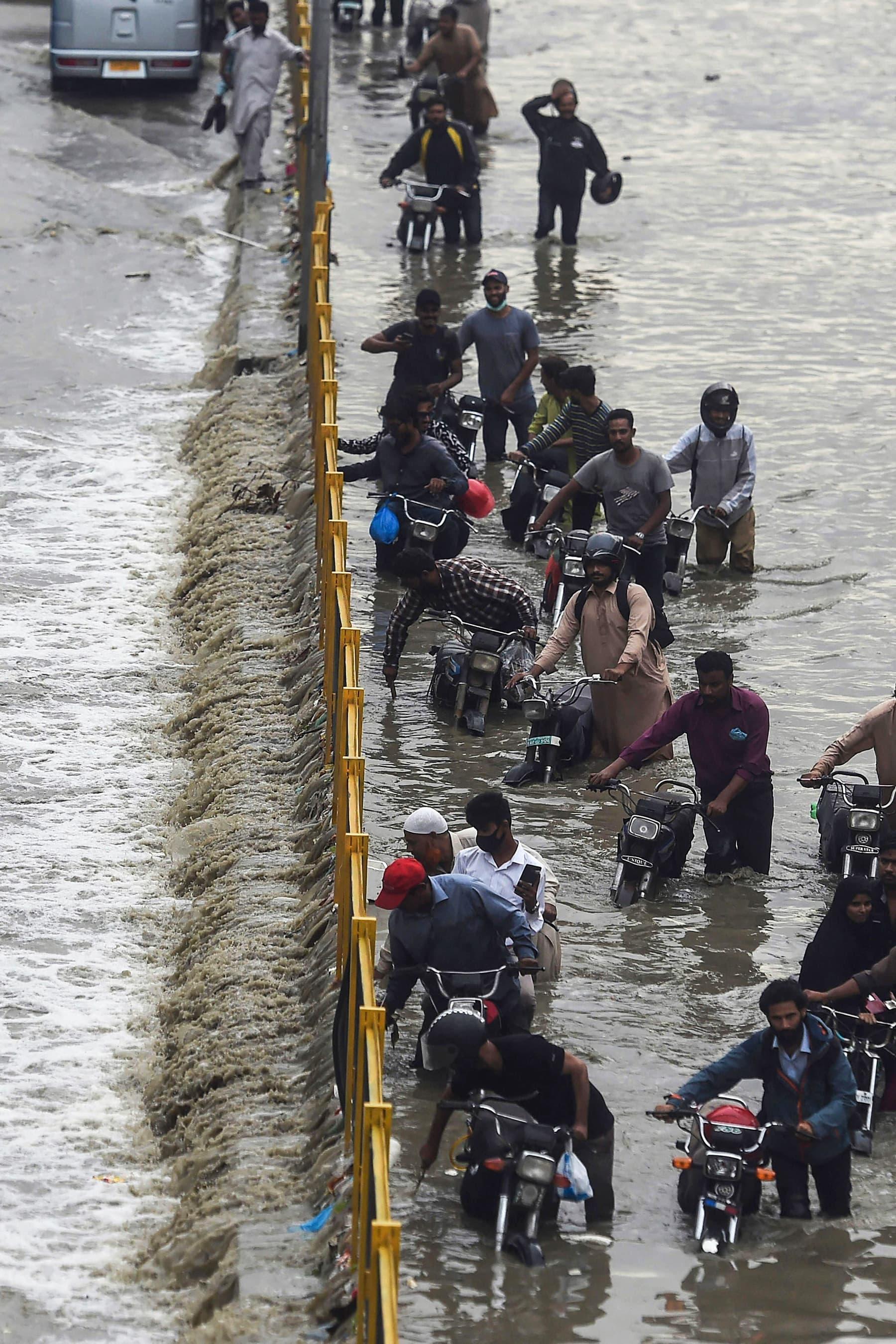 Commuters cross a flooded street after heavy rainfall in Karachi on September 23. — AFP