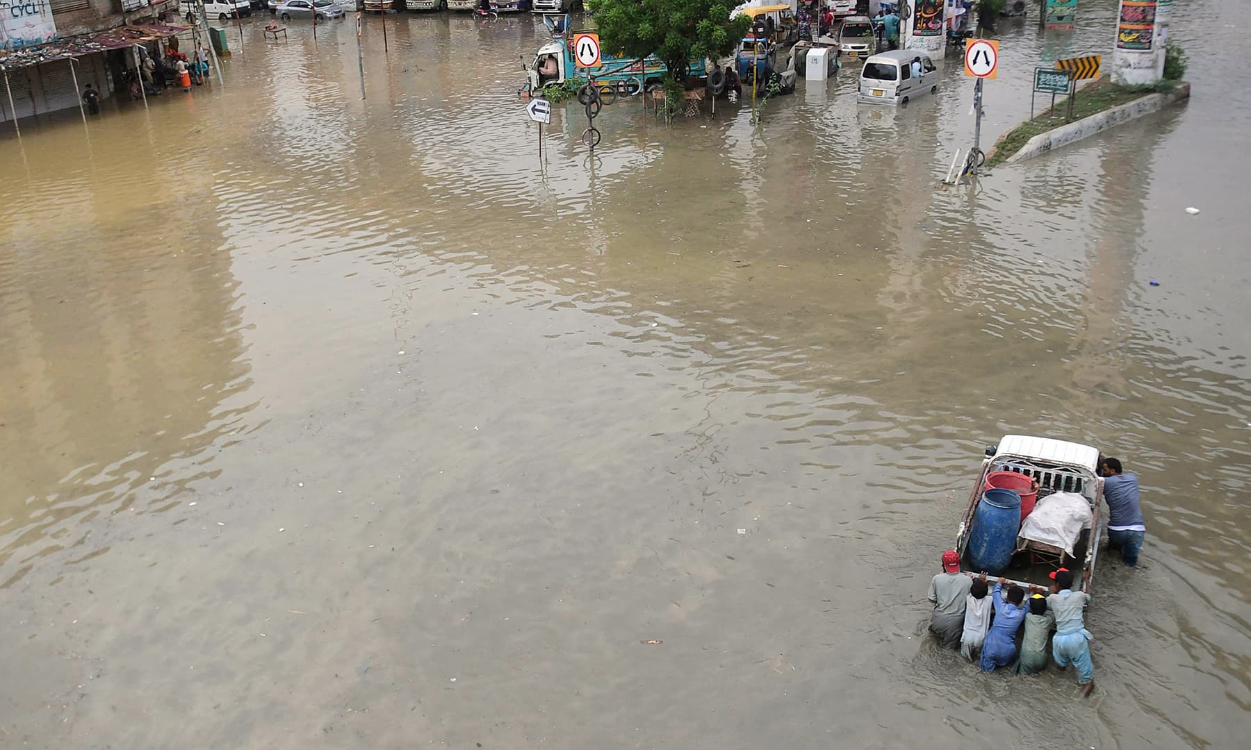 Men push a vehicle through a flooded street after heavy rainfall in Karachi on September 23. — AFP