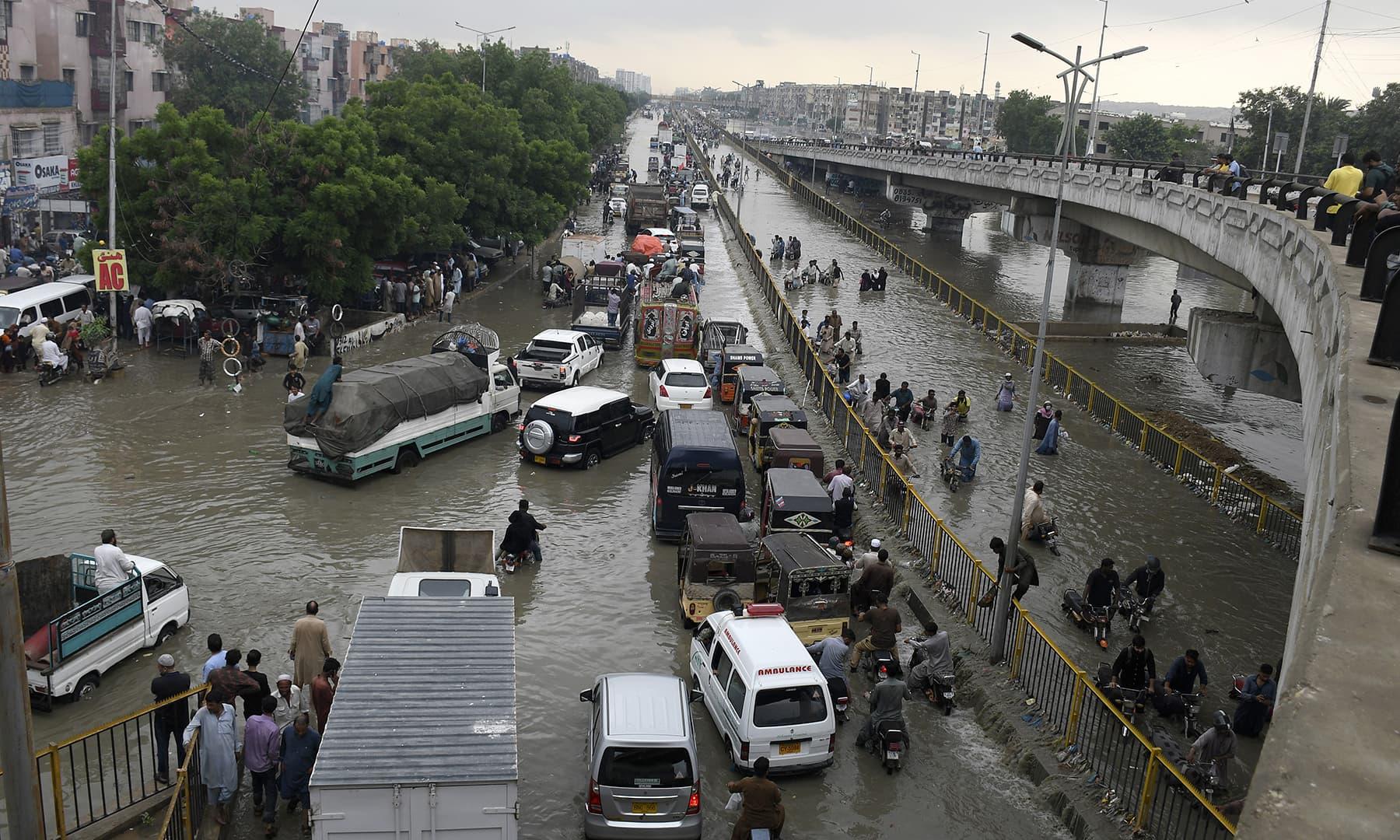 Vehicles drive through a flooded road after heavy rainfall in Karachi, Thursday, Sept 23. — AP