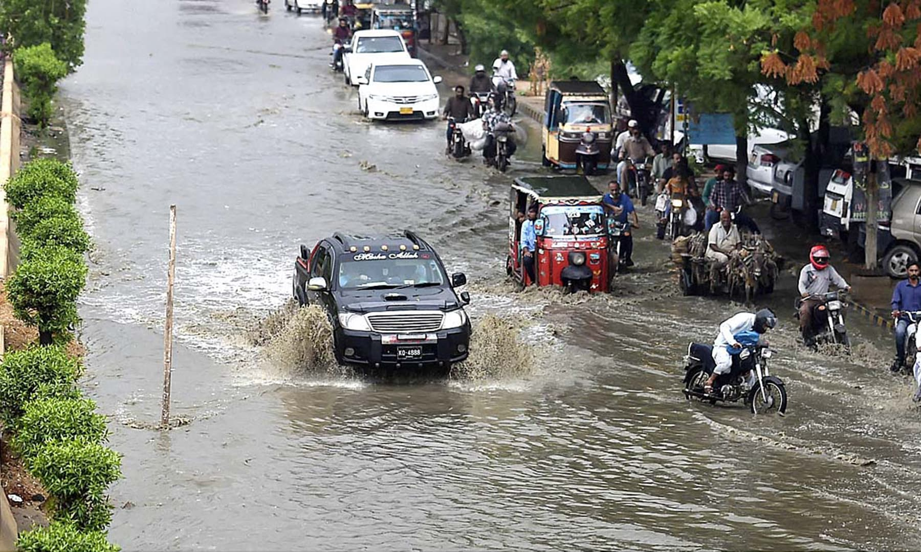 Vehicles pass through a flooded road during rain in Karachi's Buffer Zone area. — APP