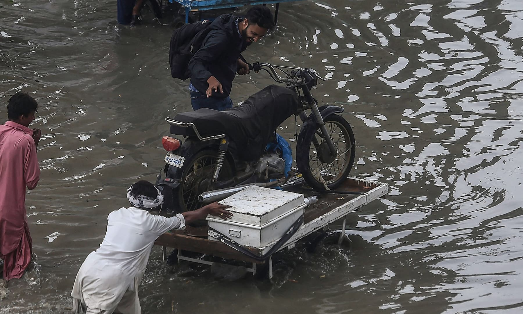 A man pushes his cart carrying a motorcyclist through a flooded street after heavy rainfall in Karachi. — AFP